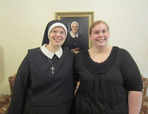 Amanda Raderstorf (right) visits with Sister Cecilia at the motherhouse of the Sisters of St. Joseph the Worker in Walton, Ky. Mother Ellen Curran, the foundress of the order, is pictured in the background. (Photo provided)