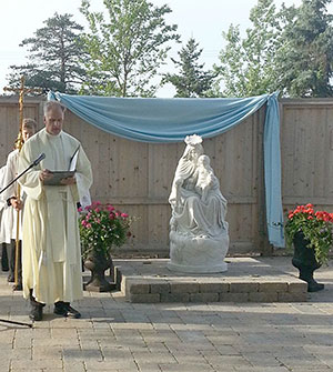 Father Richard Doerr prays during the blessing and dedication of the new Marian Prayer Garden. (Photo by Brigid Curtis Ayer)