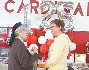 Sister Suzanne Clark, OSF, a former Sacred Heart School principal, and parishioner Pam Windler visit during a pancake breakfast. (Photo by Caroline B. Mooney)