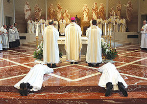 The ordinands lay prostrate on the floor during the litany of saints. (Photo by Bob Nichols)